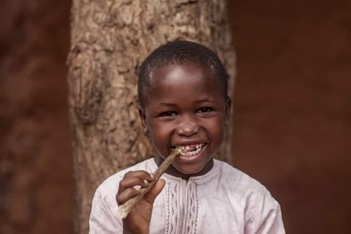 a boy smiling with dongoyaro stick in his mouth and posing for a photograph in sokoto city